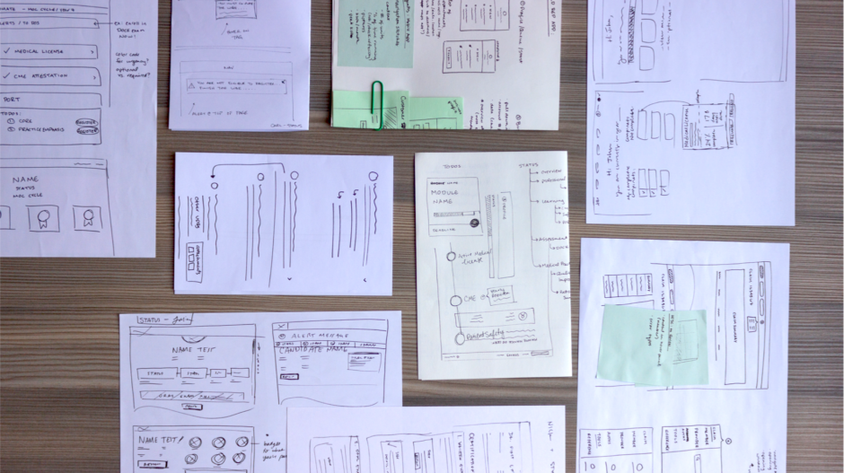 A tabletop covered in wireframe sketches to describe enterprise UI design systems
