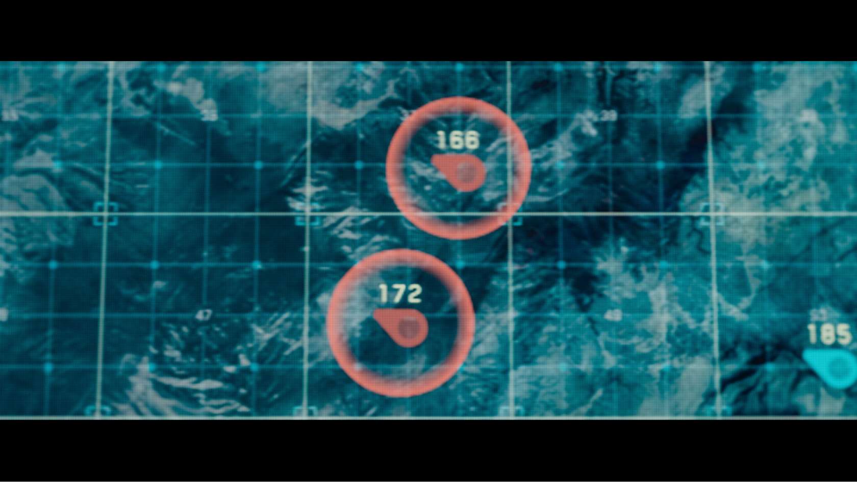 Large touch-based light table from the movie Oblivion cropped in to data that is showing alerts. The use of red in the interface design in Oblivion is provides valuable contrast against the blue-green landscape.