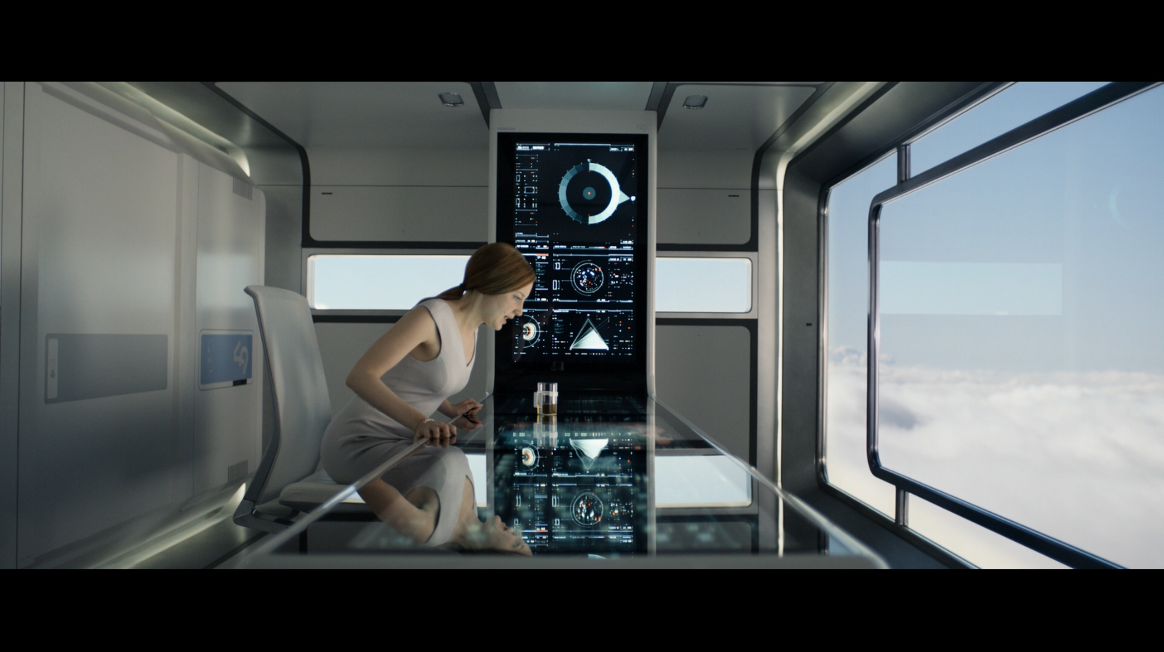 Victoria from the movie Oblivion seated at a large touch-based interface grabbing an icon that represents a drone