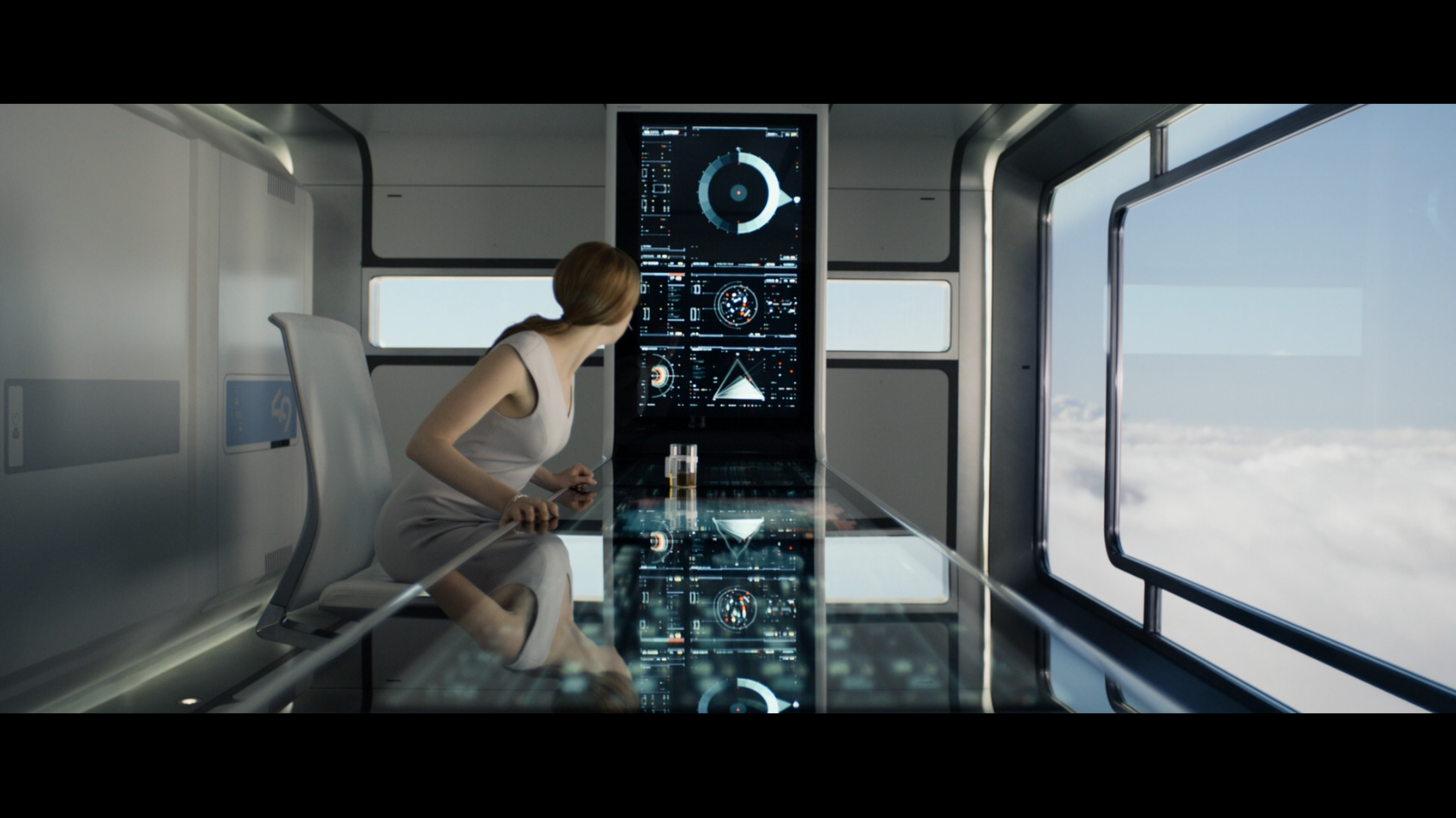 Victoria from the movie Oblivion seated at a large touch-based interface