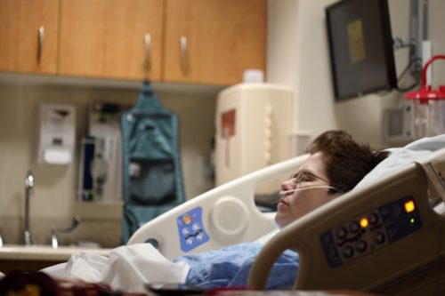 A patient reclined in a hospital bed. Patients can benefit from a variety of healthcare technology.