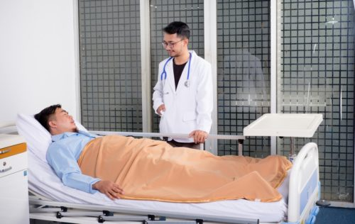 A doctor speaking with a patient in a hospital bed. Doctors can also benefit from the use of healthcare technology