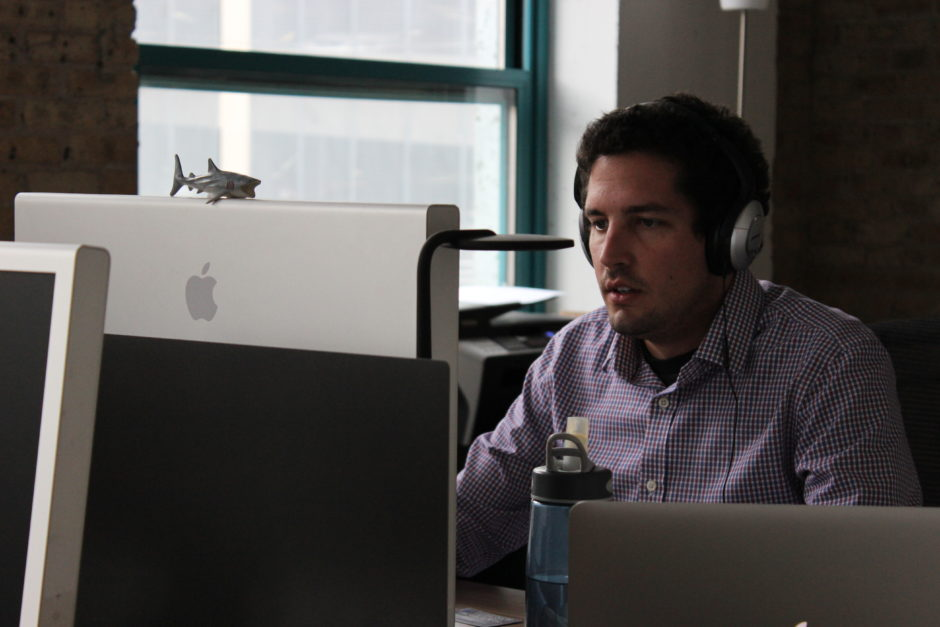 A man with headphones on working at his computer screen.