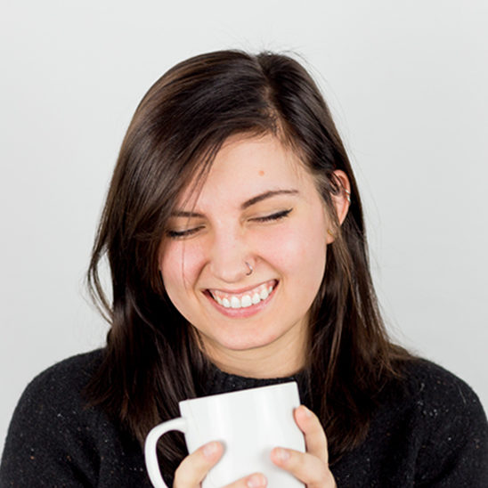 Woman holding coffee cup smiling