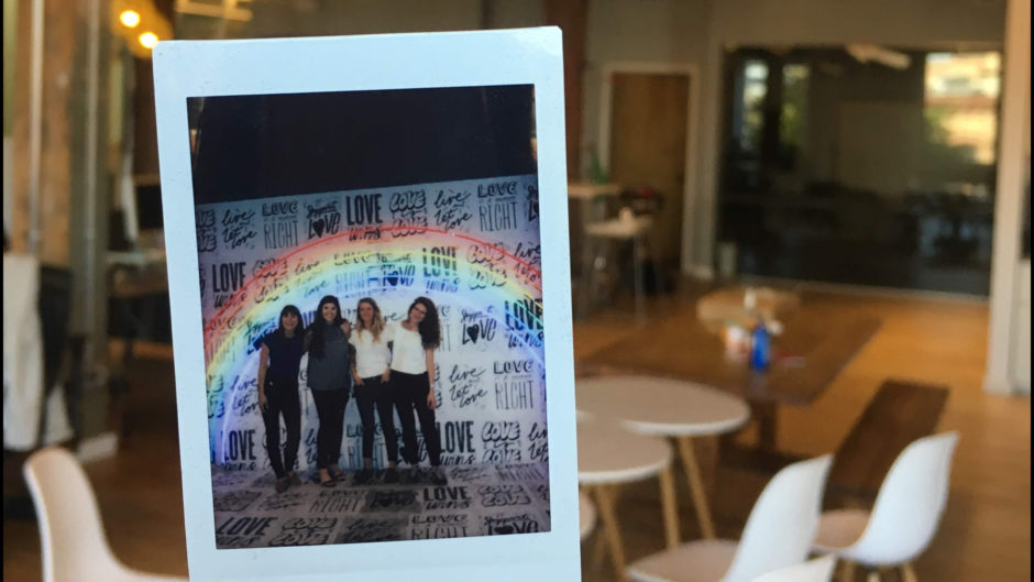 Polaroid of four women against a background that has several phrases about love written on it and a large neon rainbow overhead