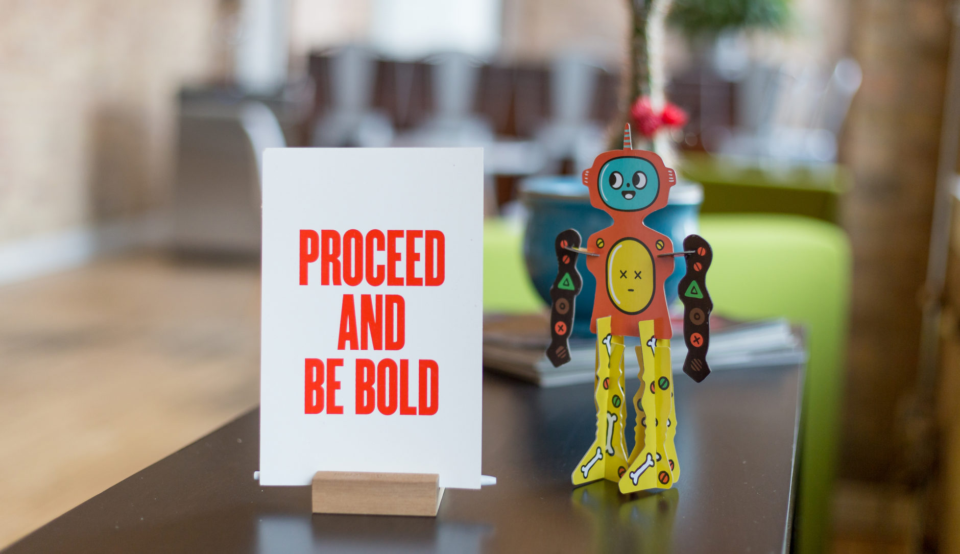 "A white card with red letters reading ""Proceed and be bold"" next to a cardboard cutout robot figurine"