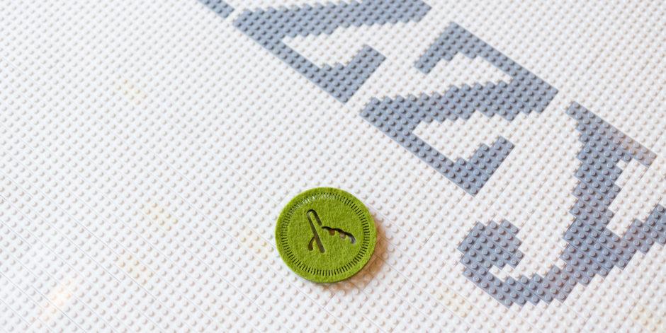 Green Fuzzy Math logo coaster on table made of Legos