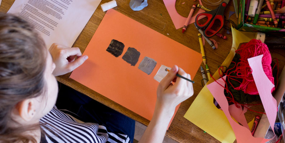 Woman painting black to white gradient squares on an orange sheet of paper