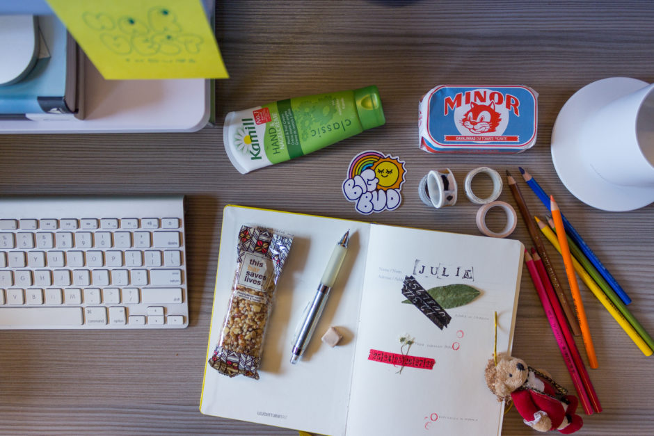 A photo of a desk taken from the top down. The desk has an open notebook with doodles, leaves, colored pencils, a cup of coffee, and other assorted knick-knacks