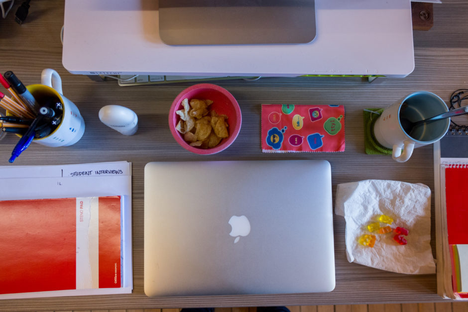 A photo of a desk taken from the top down. The desk has a closed Macbook, a coffee cup full of pens and pencils, a small bowl of snacks, an open notebook, and an empty coffee cup.
