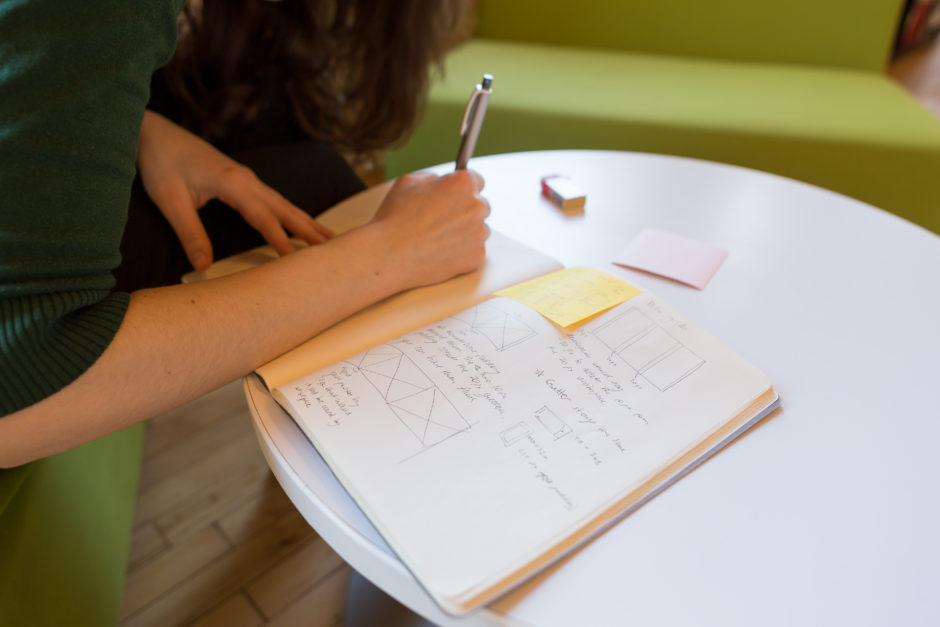 A UX design team of one is working alone, sketching in a notebook