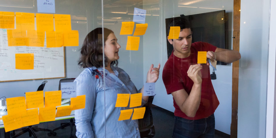 Two Fuzzy Math UX researchers working at a glass wall with sticky notes on it. One person is talking and gesturing while the other is writing on a sticky note on the glass wall.