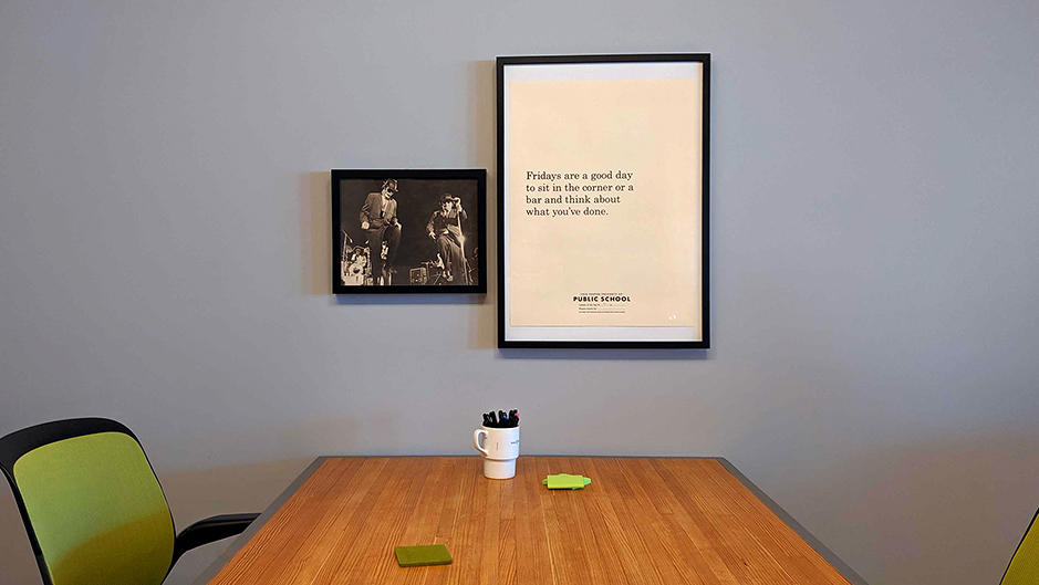 "A large, plain poster that reads ""Fridays are a good day to sit in the corner or a bar and think about what you've done,"" and a black and white photo of the blues brothers hang above a wooden table."