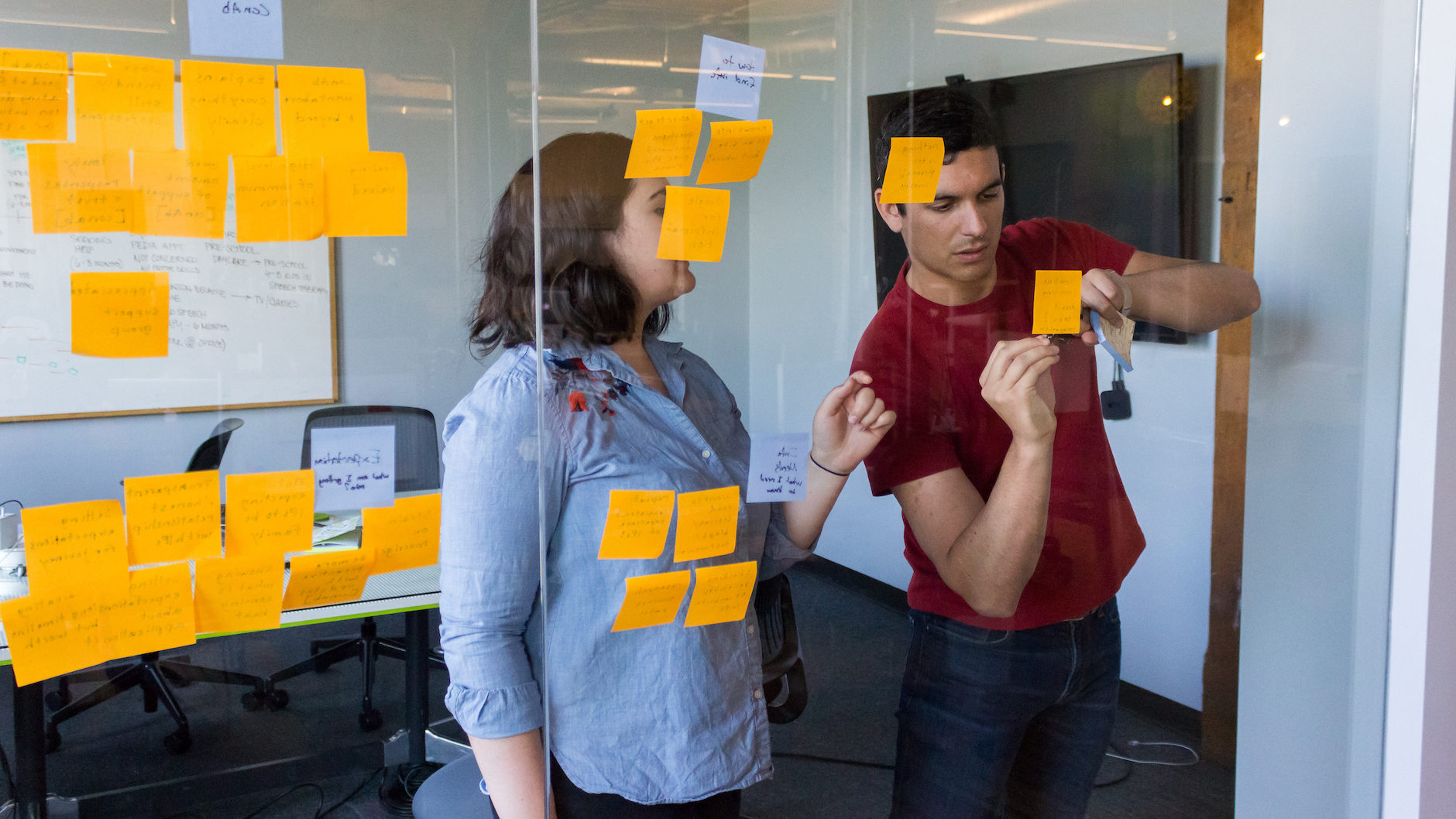 Two Fuzzy Math UX researchers are conducting synthesis of user experience testing research, working at a glass wall with sticky notes on it. One person is talking and gesturing while the other is writing on a sticky note on the glass wall