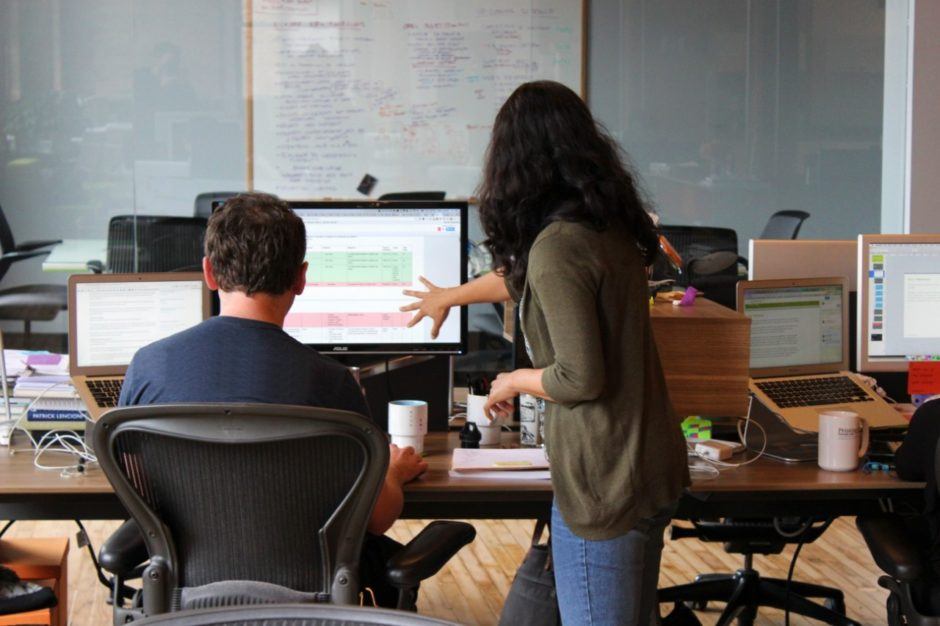 Two UX designers evaluating the end user experience of a product and looking at a computer screen. One is sitting down at the computer, and the other is standing, gesturing to the screen.