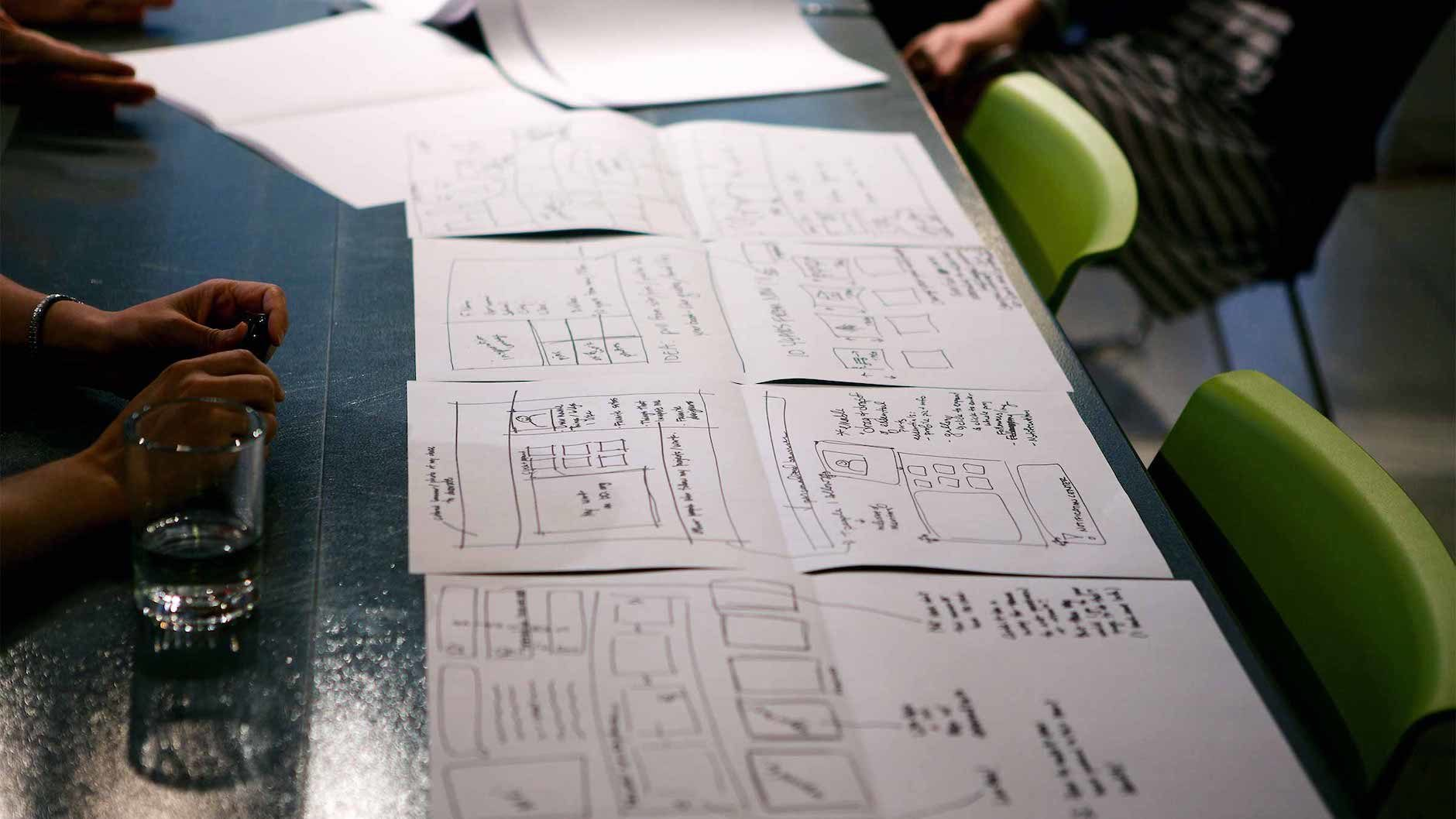 A collection of sketches lined up on a desk to illustrate information architecture in UX design
