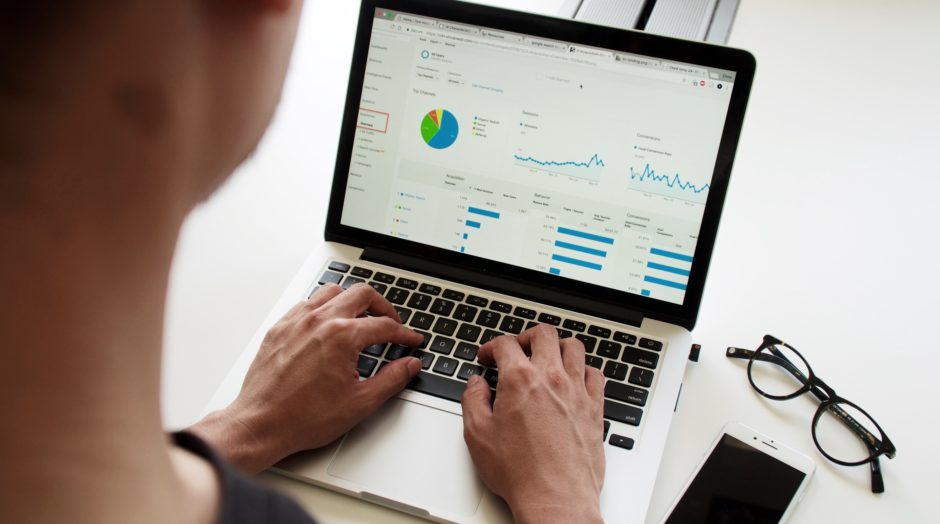 Over-the-shoulder view of a computer screen with various charts and graphs to illustrate a business leader monitoring KPIs for your design department