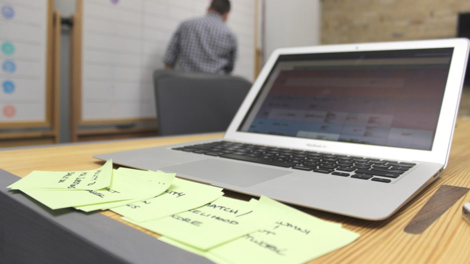 A laptop sitting on a desk. There are light green sticky notes on the desk describing the difference between user experience and usability. There is a UX designer writing on a whiteboard in the background.