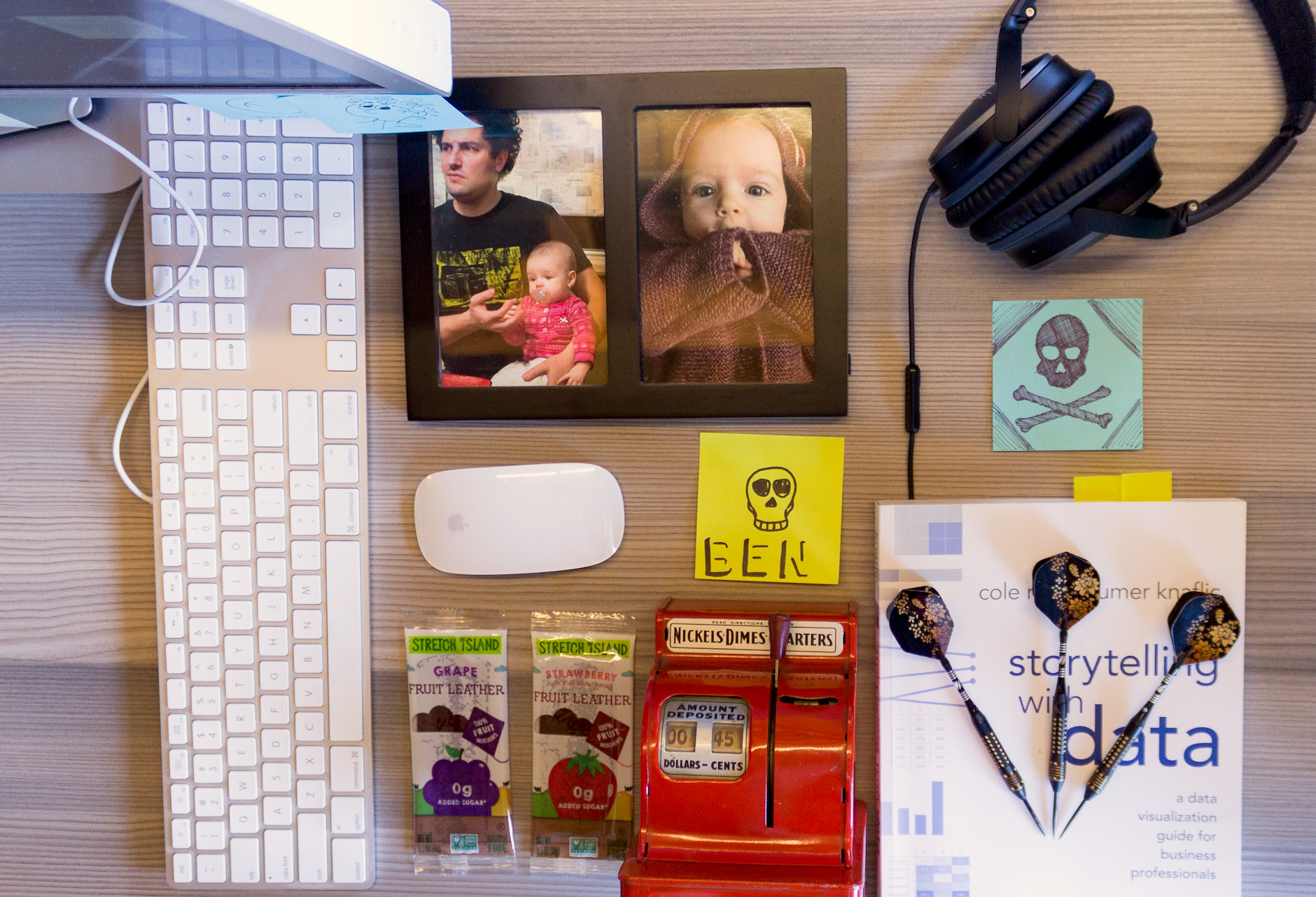 An overhead shot of Fuzzy Math co-founder Ben's desk, including framed photos of his two daughters, headphones, darts, and a sticky note with a skull and crossbones doodle.