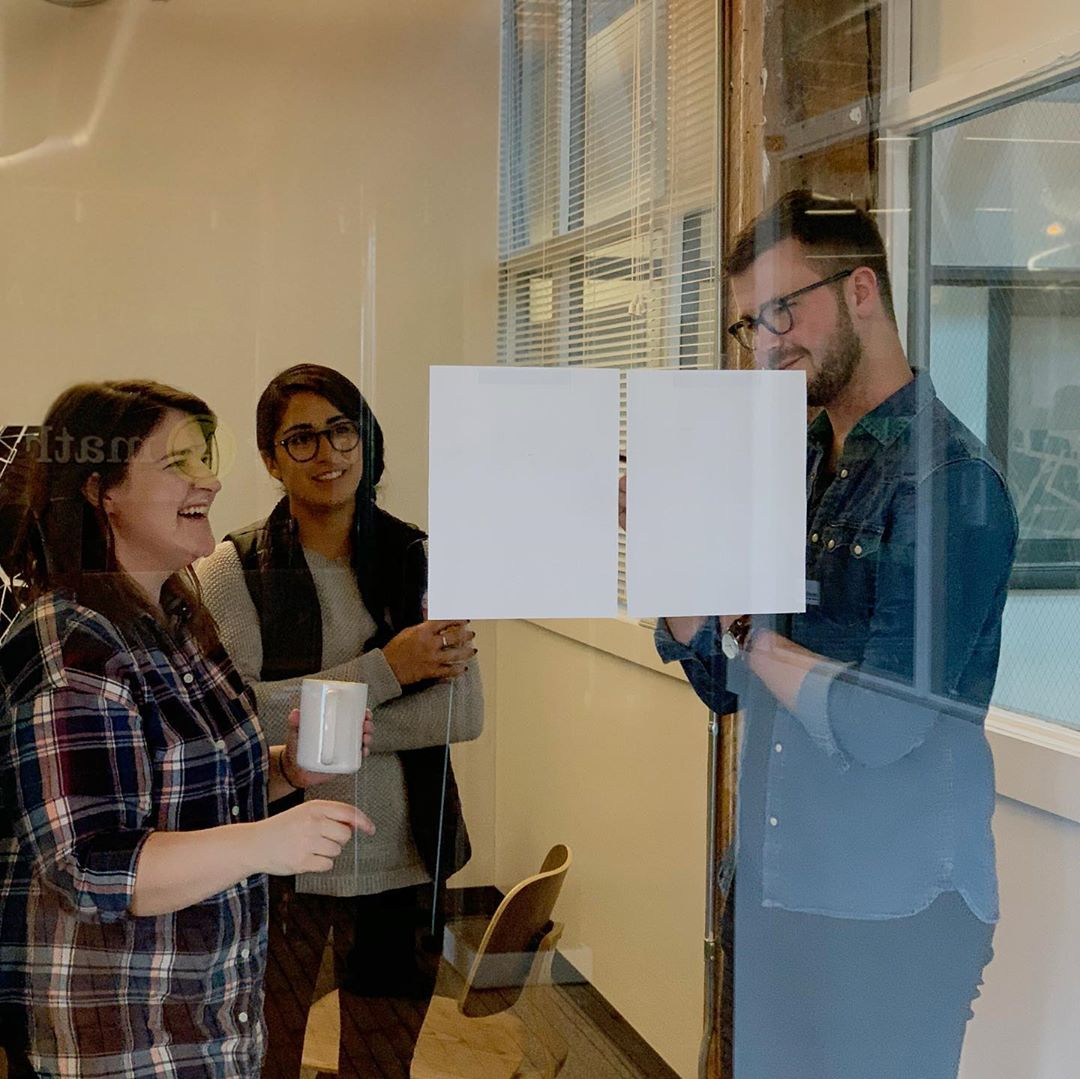 Three UX designers are gathered around a two printed wireframes to give and receive cross-project feedback.