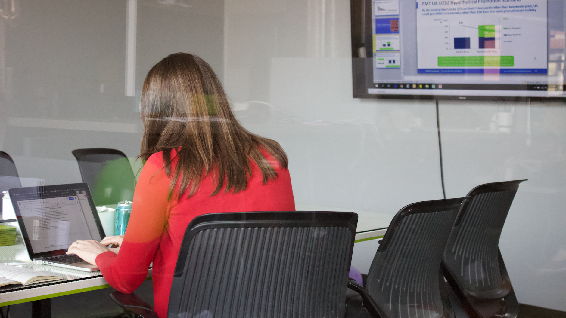 A designer sits at a conference room table, ready for a remote meeting in Zoom