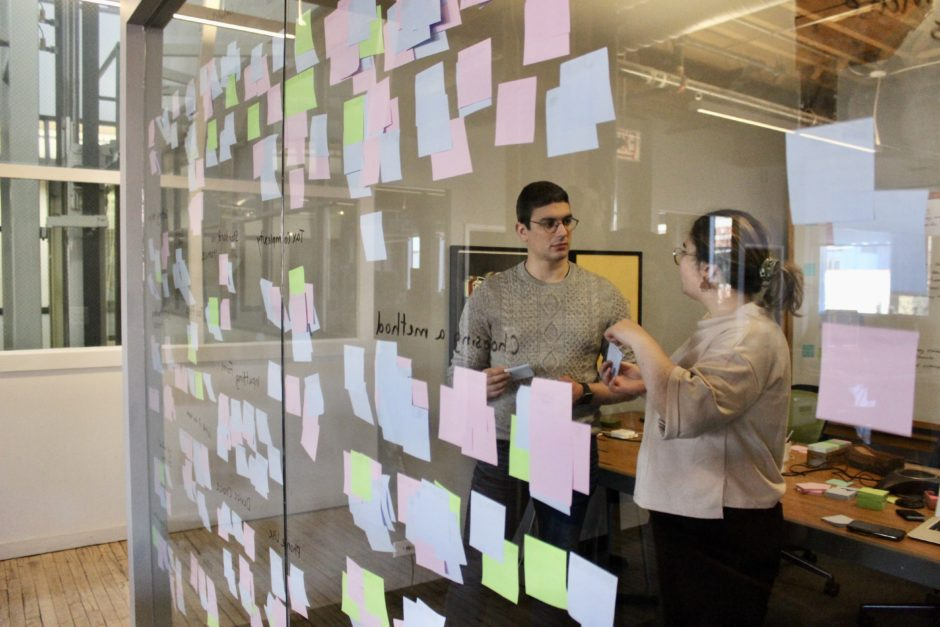 Two people synthesizing enterprise software UX design research