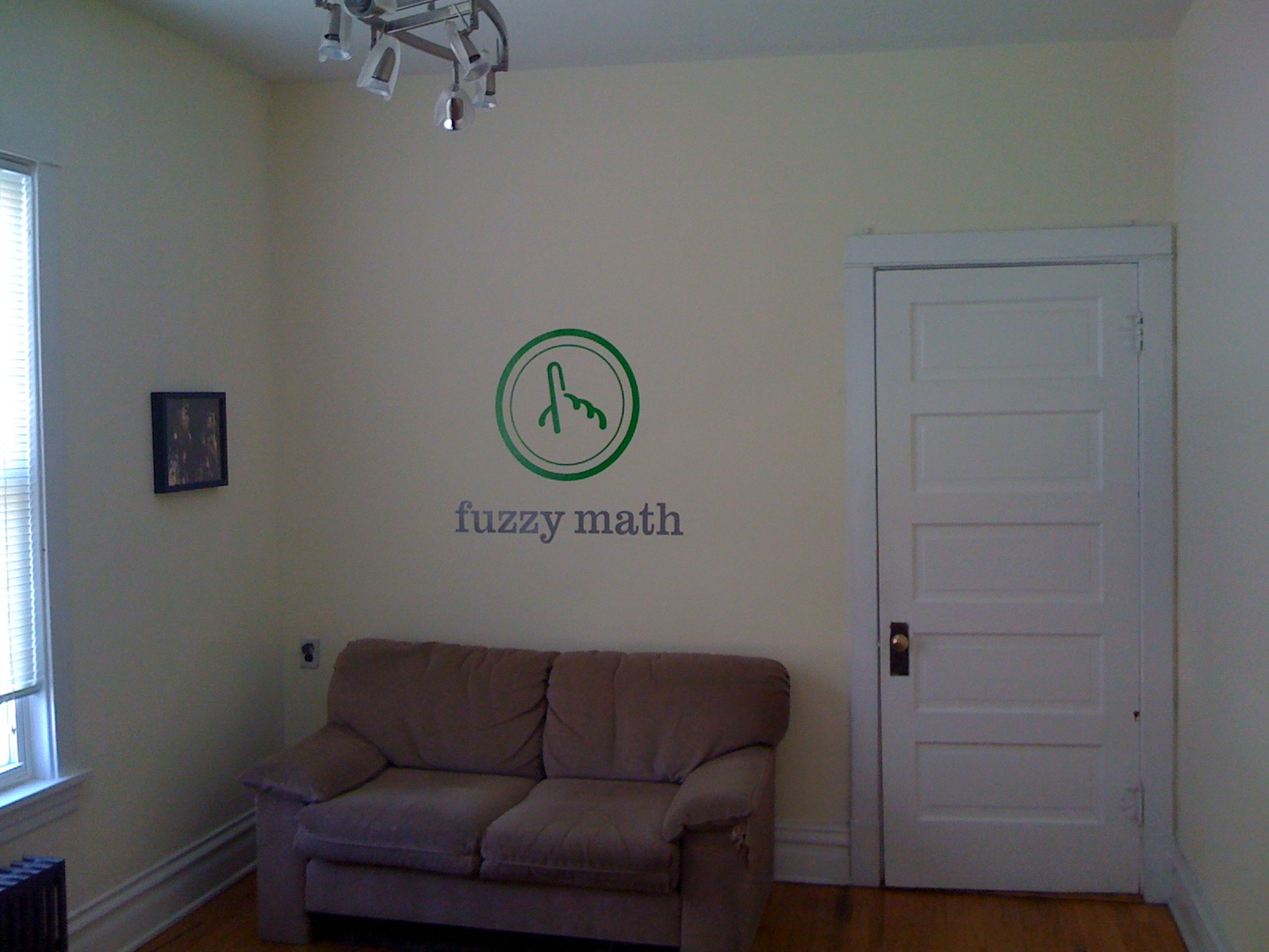 A small room with a couch, window, door, and Fuzzy Math logo on the wall.
