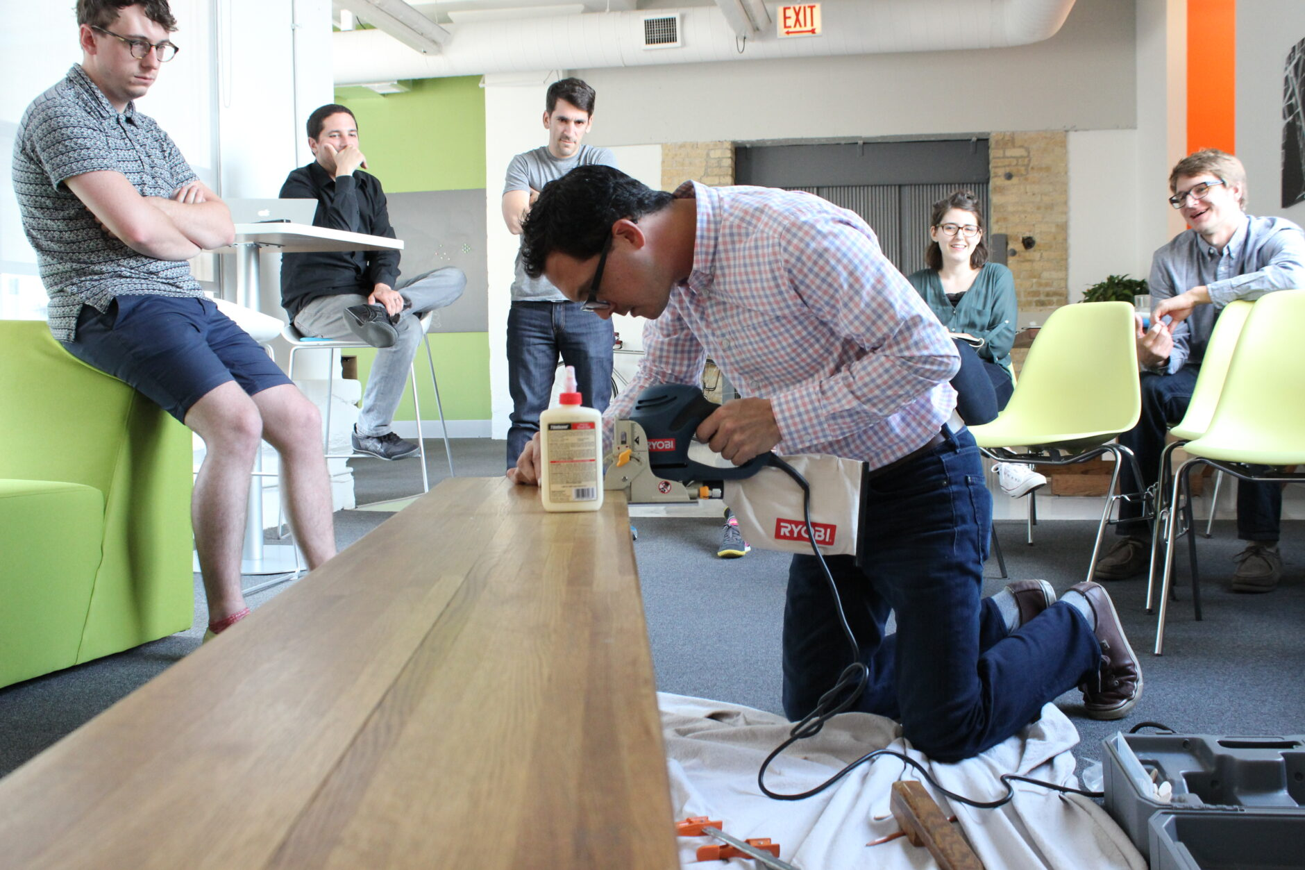 Mark building a bench during a skill share activity surrounded by co-workers watching in amusement.